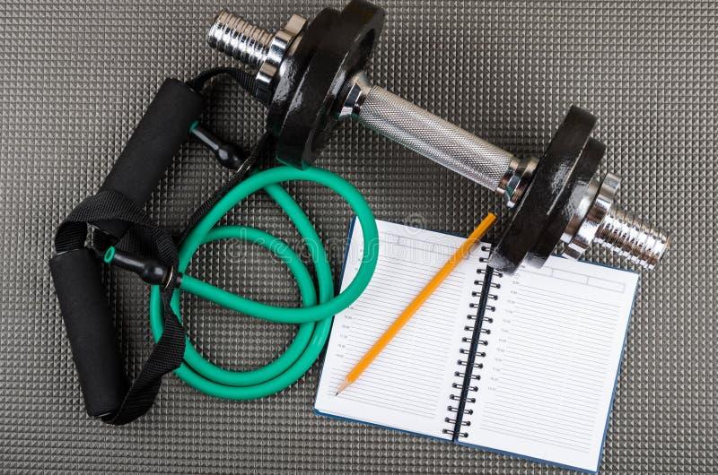 橡胶筒形扩展器、可调整的哑铃、笔记薄和铅笔 免版税库存图片