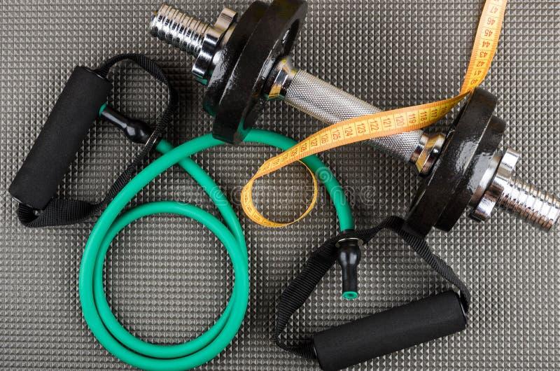 橡胶筒形扩展器、可调整的哑铃和措施磁带 库存照片