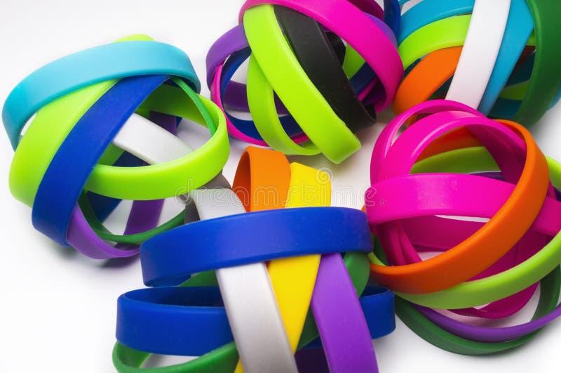 橡胶镯子 硅树脂时尚圆的社会镯子穿戴 白色backgroundRainbow颜色,橡皮筋 五颜六色的wristba 免版税库存图片