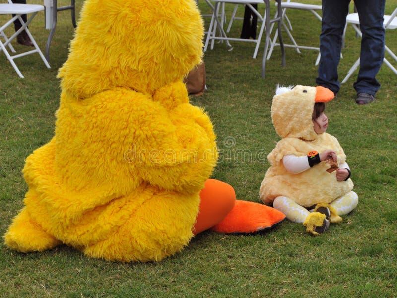 橡胶鸭子服装的小孩和橡胶鸭子吉祥人分享片刻在橡胶鸭子节日 免版税库存图片