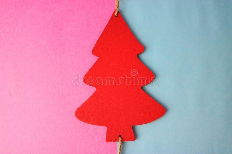 欢乐与一棵小玩具木红色和白色逗人喜爱的圣诞树的新年的圣诞节多彩多姿的快乐的蓝色桃红色背景 免版税库存图片