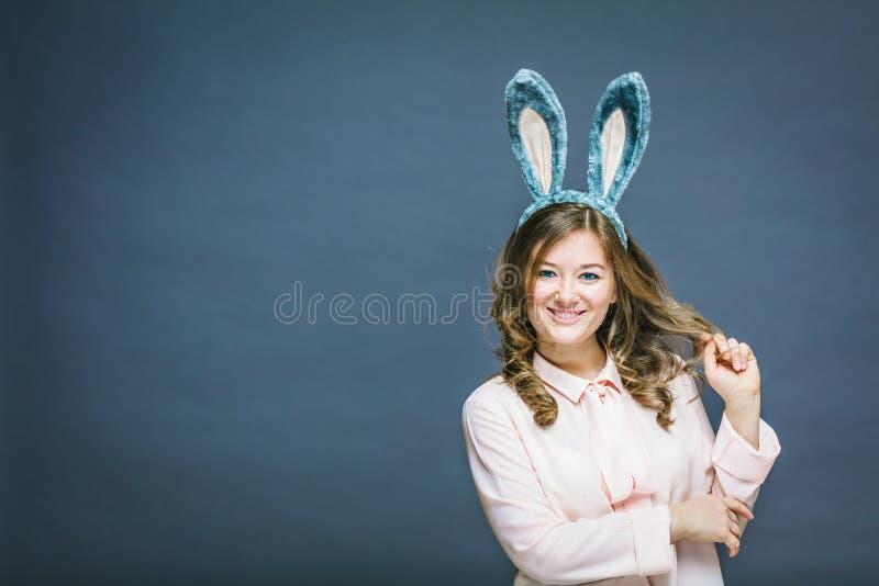 欢乐兔宝宝和蛋季节 在灰色背景隔绝的复活节兔子耳朵的愉快的现代妇女 免版税库存图片