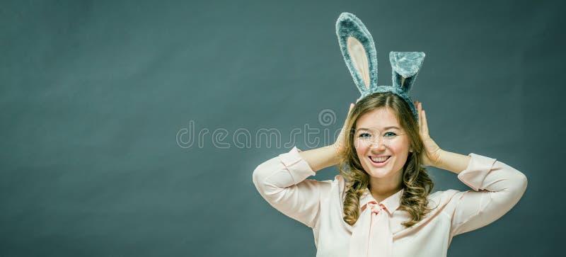 欢乐兔宝宝和蛋季节 在灰色背景隔绝的复活节兔子耳朵的愉快的现代妇女 库存照片