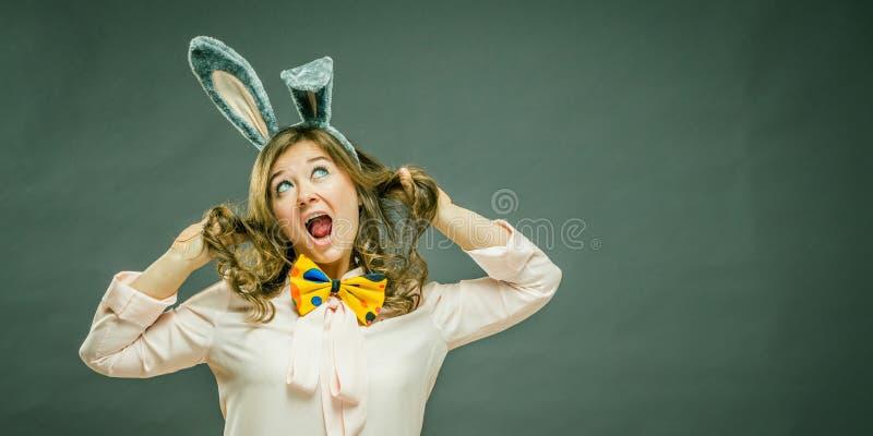 欢乐兔宝宝和蛋季节 在灰色背景隔绝的复活节兔子耳朵的愉快的现代妇女 免版税库存照片