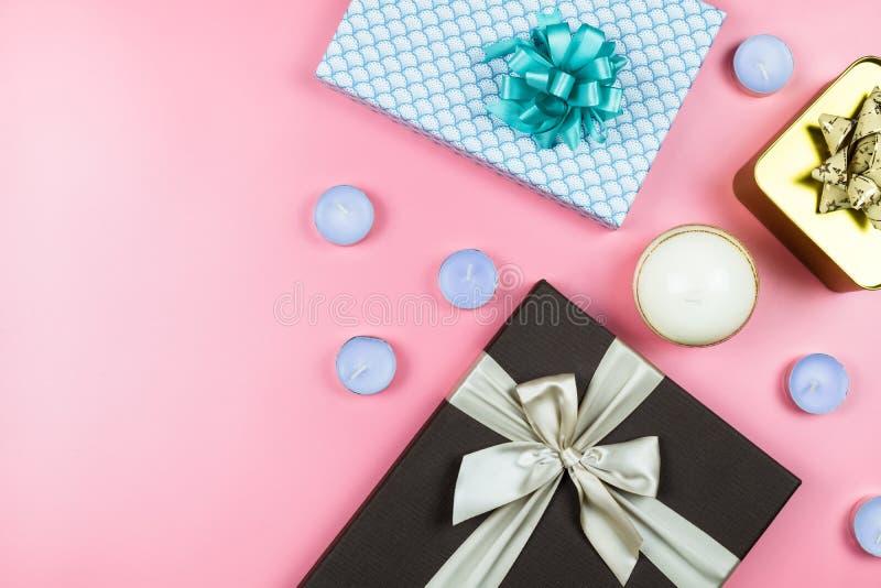 欢乐圣诞节背景-在桃红色背景的3个礼物盒与茶光蜡烛 免版税库存照片