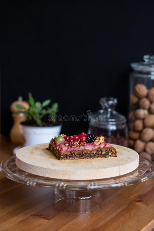 欢乐坚果饼片断用奶油色和糖煮的莓果和被轰击的核桃在defocused背景 免版税图库摄影