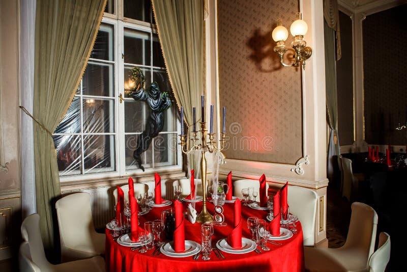 欢乐宴会桌在红色和黑颜色的哥特式样式服务 免版税库存图片