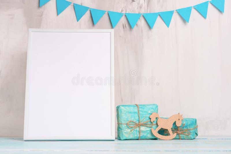 欢乐心情、儿童的诗歌选有一个白色空的框架的设计和玩具有礼物布局的 婴孩出生的男孩看板卡新的阵雨 免版税库存图片