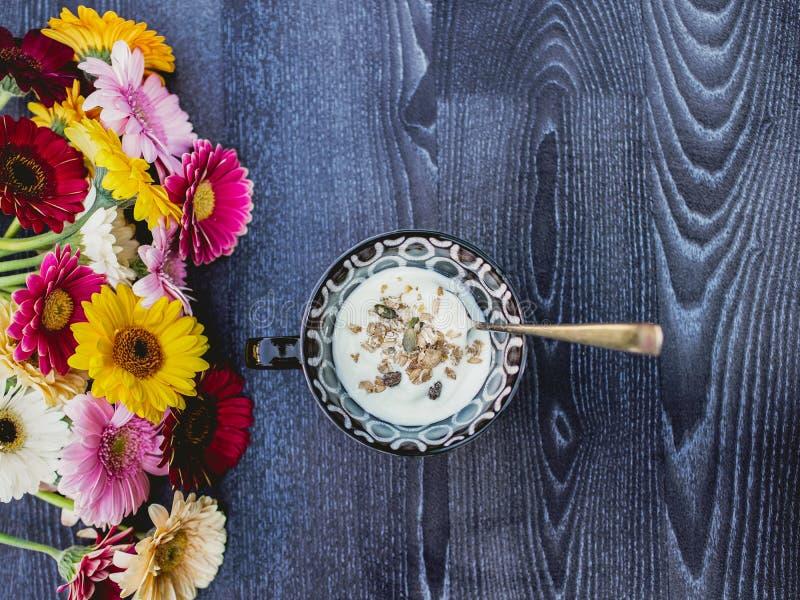 欢乐早餐、五谷muesli用酸奶用酸奶和五颜六色的大丁草花在木深蓝vackground 免版税图库摄影
