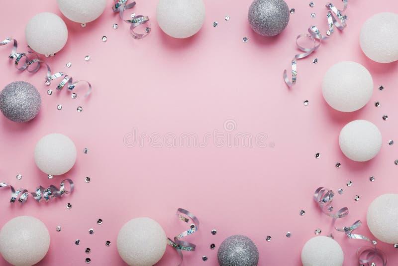 欢乐框架由圣诞节球和衣服饰物之小金属片做成在桃红色台式视图 背景计算机方式模仿屏幕 平的位置 党大模型 免版税图库摄影