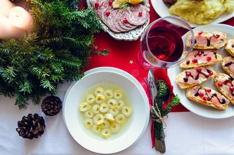 欢乐桌设置平位置假日晚餐的与盘 传统意大利圣诞晚餐-意大利式饺子用汤, 库存图片