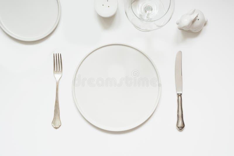 欢乐现代白色桌设置 板材和利器在白色 在视图之上 免版税库存照片
