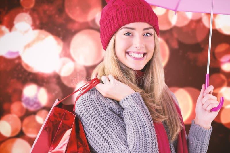 欢乐白肤金发的举行的伞和袋子的综合图象 免版税库存图片