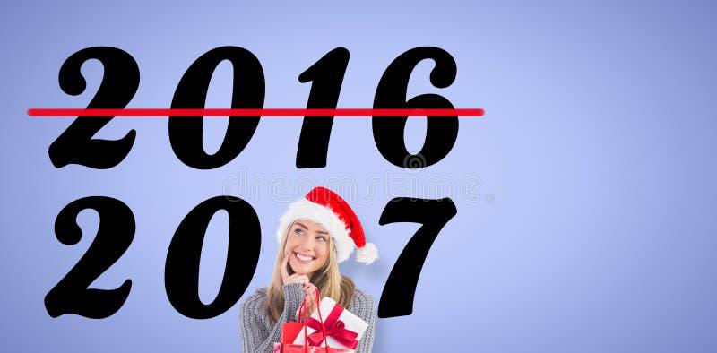 欢乐白肤金发的举行的圣诞节礼物和袋子的综合图象 免版税库存图片