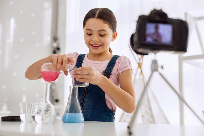 欢乐的女孩倾吐的化学制品和记录的vlog 免版税库存照片