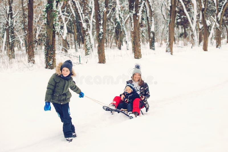 欢乐的家庭在雪地公园里 儿童和母亲在冬季玩耍 积极健康的生活方式 冬季圣诞 库存图片