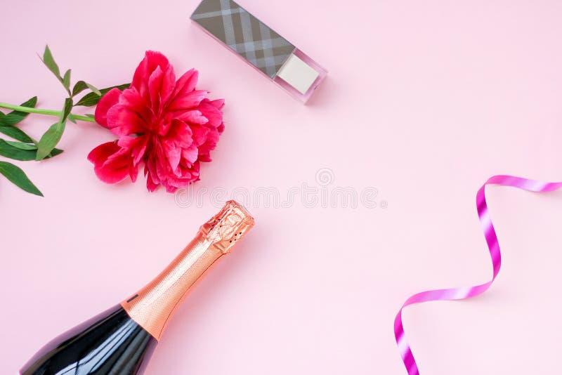 欢乐的布局女孩,一个瓶香槟,化妆用品,在桃红色背景的红色花牡丹 文本的,顶视图地方 免版税图库摄影