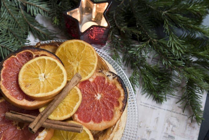 欢乐蛋糕用桔子、葡萄柚和桂香在杉木分支和星的背景 免版税图库摄影