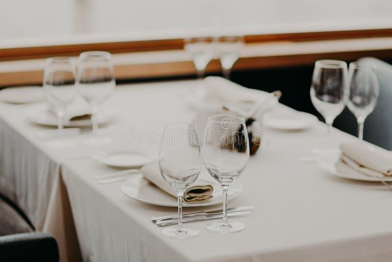 欢乐装饰的桌水平的看法与空的葡萄酒杯和板材的反对被弄脏的背景 在欢乐桌上的利器 库存照片