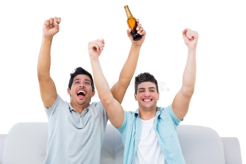 欢呼与啤酒一起的愉快的足球迷 库存照片