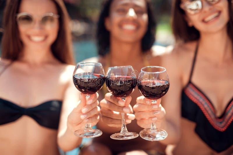 欢呼与杯的三名美丽的妇女在游泳池的酒夏令时 图库摄影
