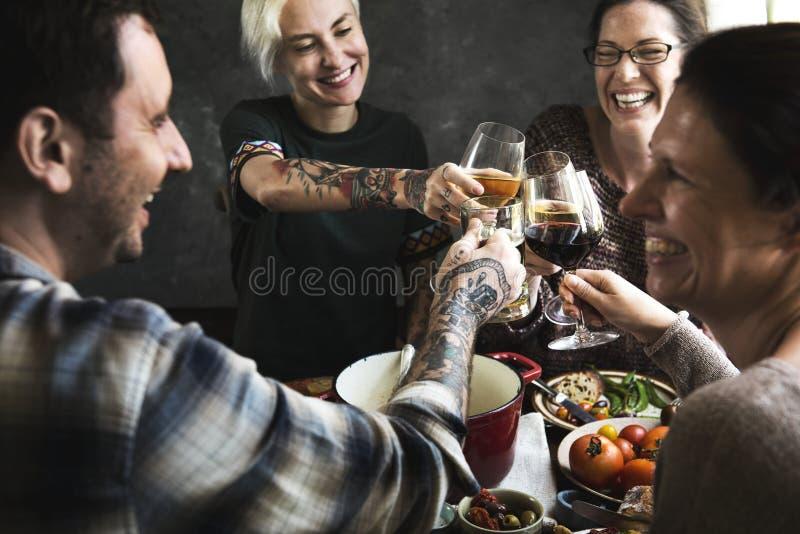 欢呼与杯的愉快的人民酒 免版税库存照片