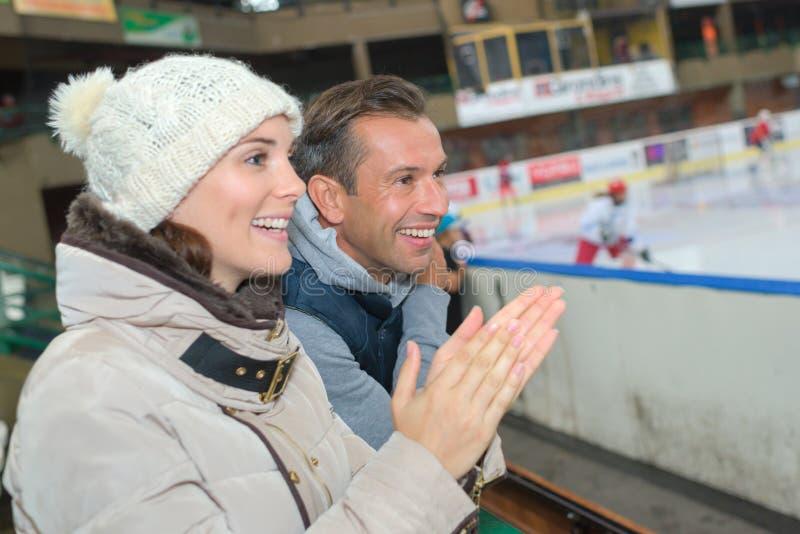 欢呼在他们的冰球队的夫妇 库存照片
