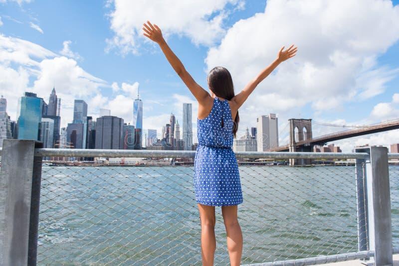 欢呼在NYC纽约都市地平线的愉快的自由妇女 免版税库存图片