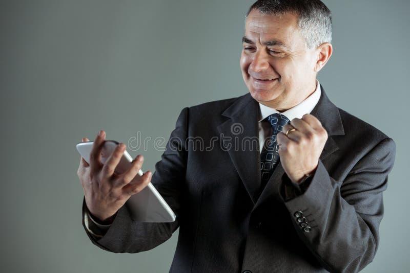 欢呼成功的欢腾的商人 库存照片