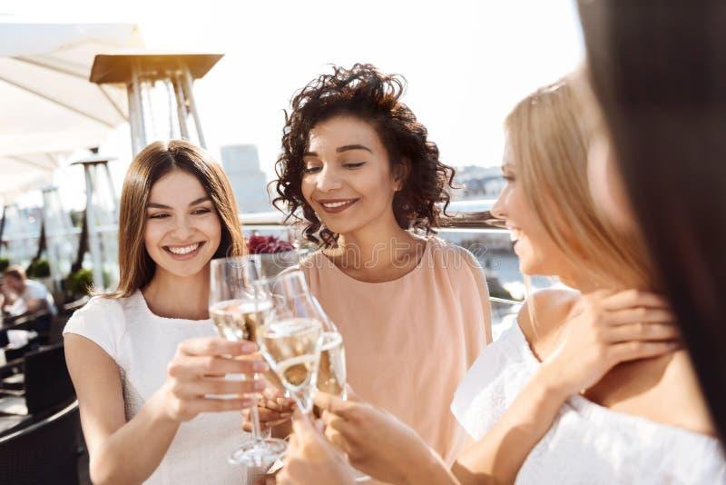 欢呼用香槟的高兴可爱的妇女 免版税库存图片