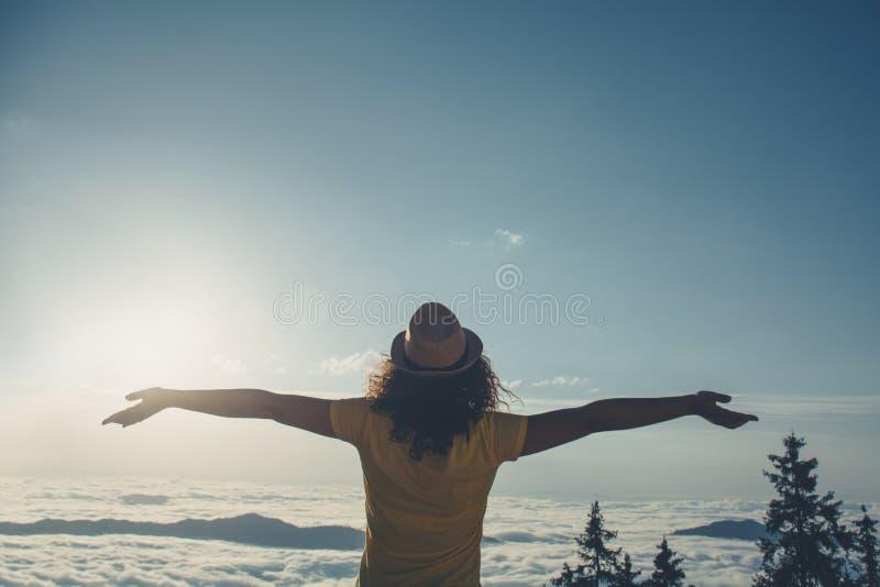 欢呼的妇女享受美丽的景色在山峰 免版税库存照片