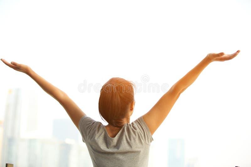 欢呼的妇女在城市张开胳膊 免版税库存图片
