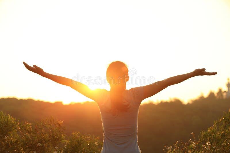 欢呼的妇女张开胳膊在日出山峰 免版税库存照片