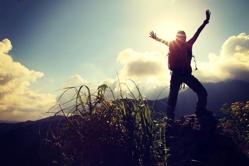 欢呼的妇女远足者张开胳膊在山峰 免版税图库摄影