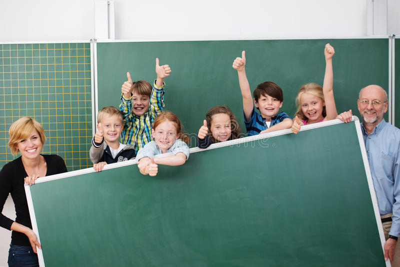 欢呼的愉快的年轻小学生 免版税库存图片