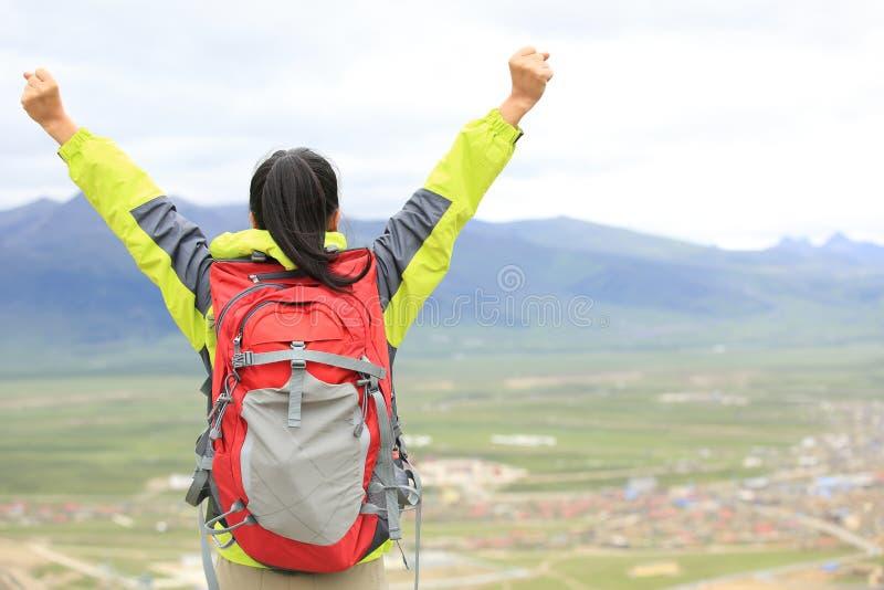 欢呼远足妇女享受美丽的景色在山峰 免版税库存图片