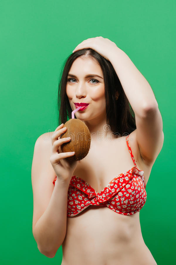 欢悦女性模型画象在喝在绿色背景的明亮的泳装的热带鸡尾酒在演播室 库存照片