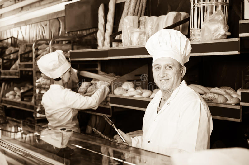 欢悦面包师用新鲜面包在面包店 库存照片