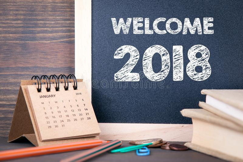 欢迎2018年 纸日历和黑板在一张木桌上 库存照片