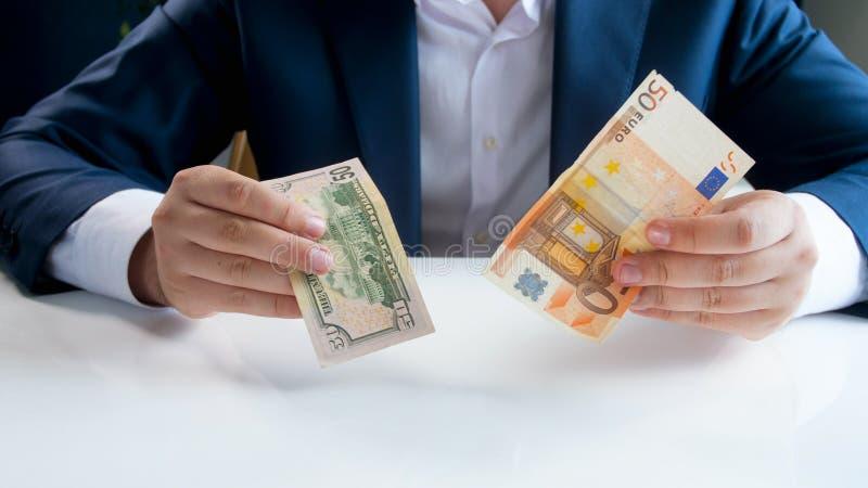 欧元和美元货币稳定概念性照片  商人在手上的拿着不同的钞票 图库摄影