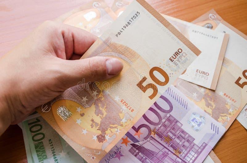 50欧元在手中以欧元钞票为背景 图库摄影