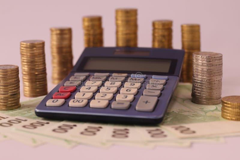 欧元硬币围拢的计算器堆积在100欧元欧元纸币  免版税图库摄影