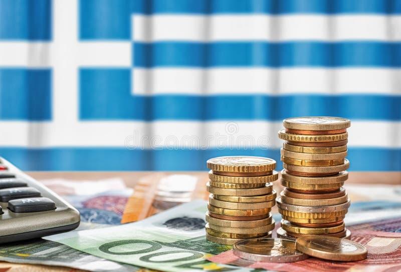 欧元钞票和硬币在希腊的国旗前面 免版税库存照片