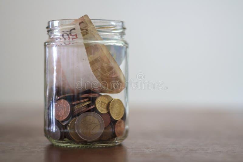 欧元钞票和硬币在玻璃瓶子 库存照片