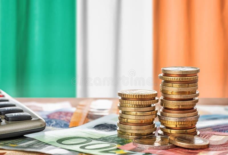 欧元钞票和硬币在Irelan前面国旗  免版税库存照片