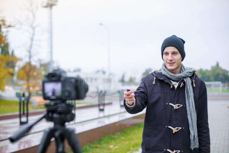 欧洲人,常设外部和拍摄在三脚架的一台现代照相机 库存照片