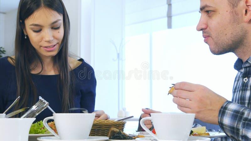 欧洲和谐家庭吃健康午餐在咖啡馆 吃菜沙拉,聊天和微笑的他们 免版税库存图片