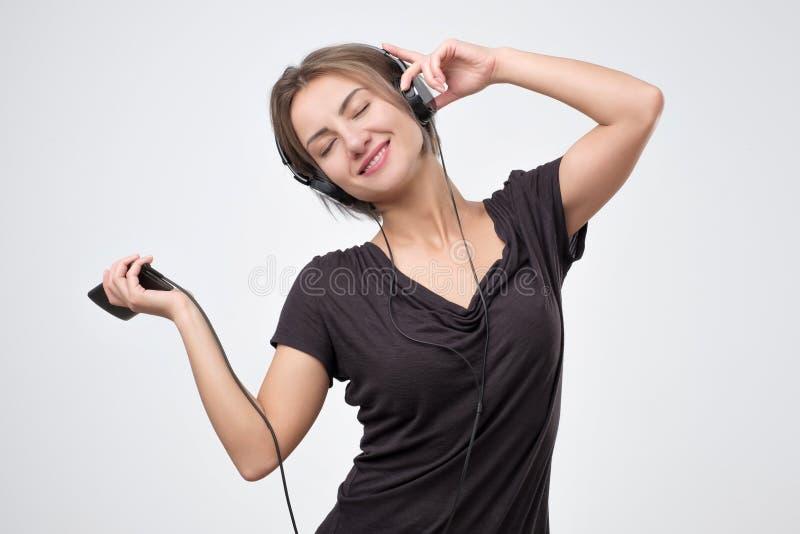 欧洲妇女快乐听到在手机的音乐 库存照片
