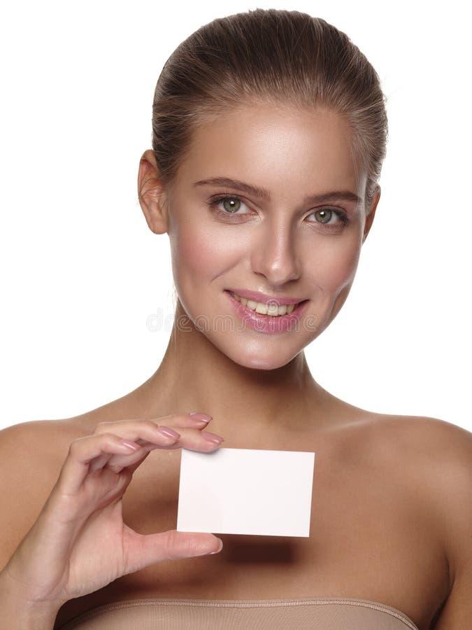 欧洲年轻微笑的女孩的画象有健康完善的光滑的皮肤的,拿着企业名片 免版税库存照片