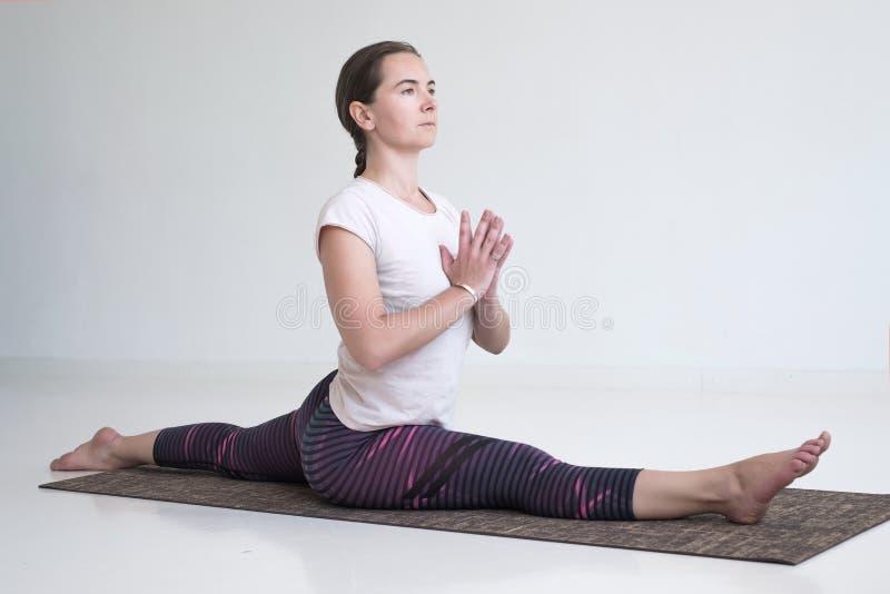 欧洲成熟做Hanumanasana的女子实践的瑜伽 库存图片